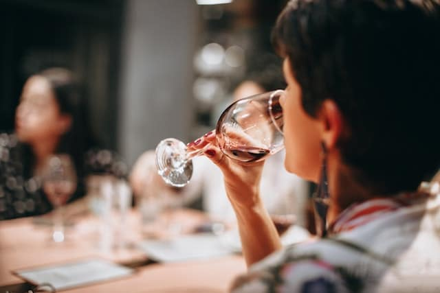 Adult woman drinking wine at restaurant